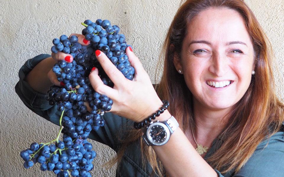 Produtora do vinho, Rita Cabral Almeida e Fonseca, a segurar num cacho de uvas